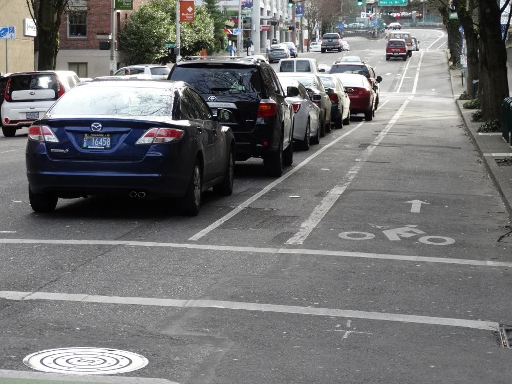 Carros estacionados, deixando uma via, à direita, para tráfego de bicicletas